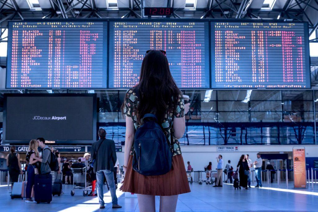 空港の発着電子案内板の前に立つスカートを履いた女性