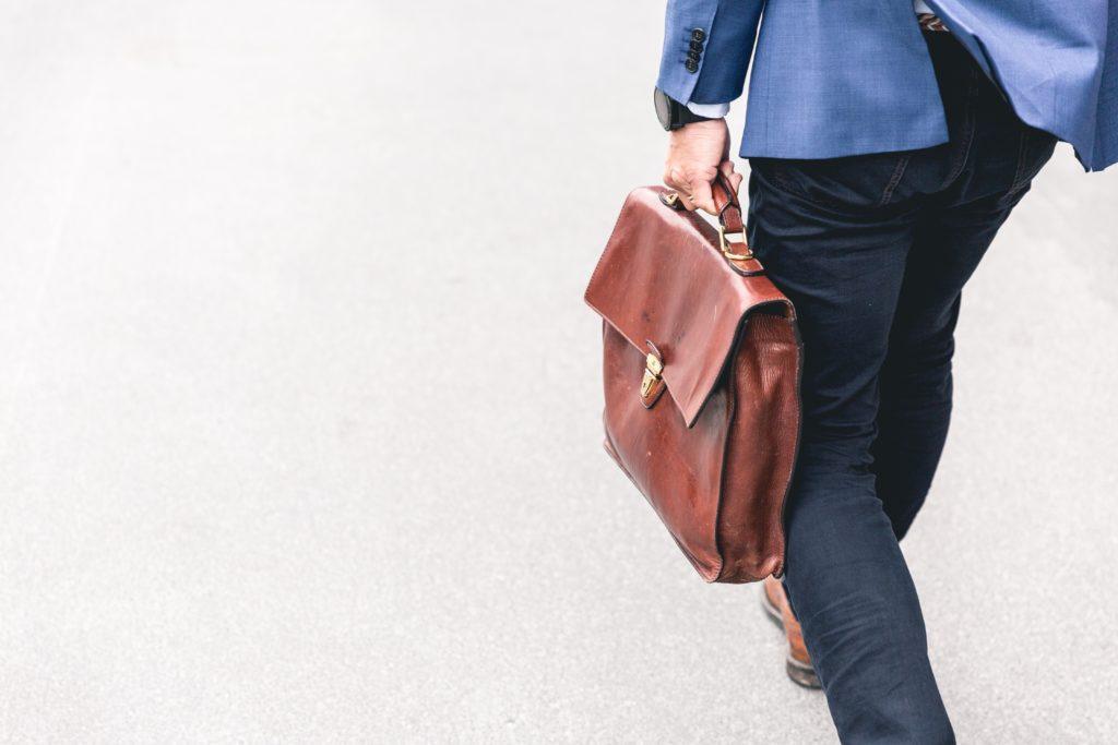 革の鞄を持って出かけるスーツの男性