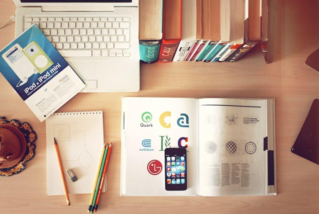 PCと本とスマホとノートを広げて勉強中