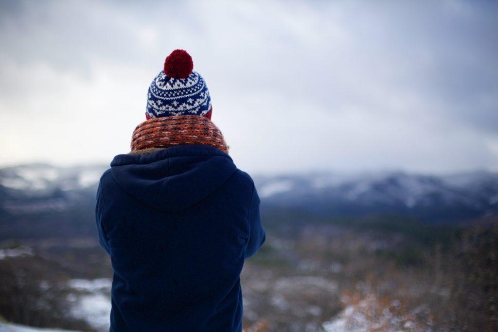毛糸の帽子とマフラーを着た人の後ろ姿
