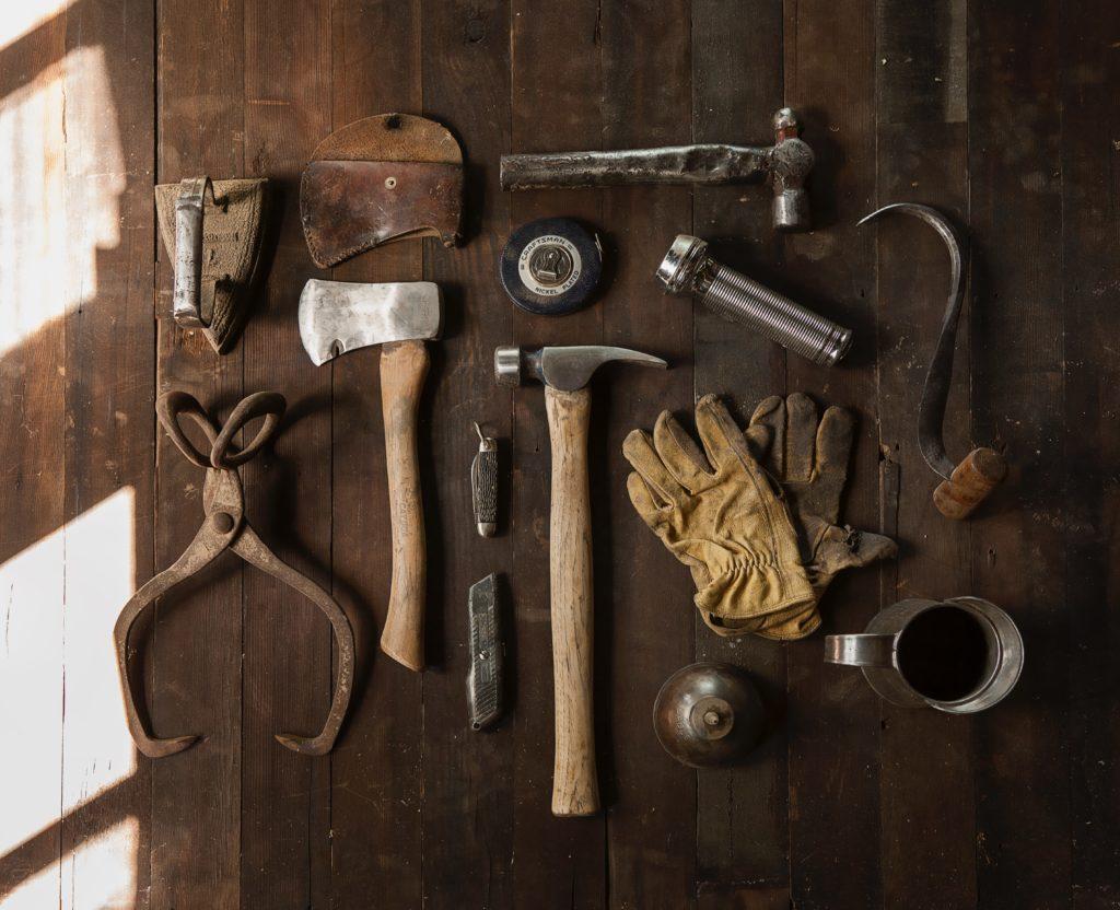 斧やハンマー、革手袋などのキャンプツール一式