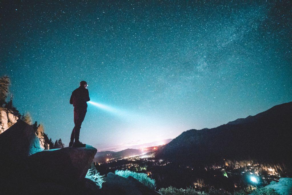 星空の下でライトを照らす人