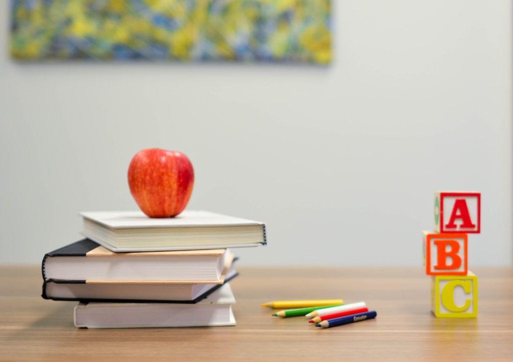 積まれた本の上にリンゴと色鉛筆とアルファベットの積み木