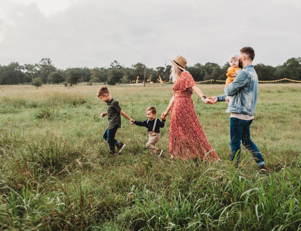 5人の家族が草原を歩いている