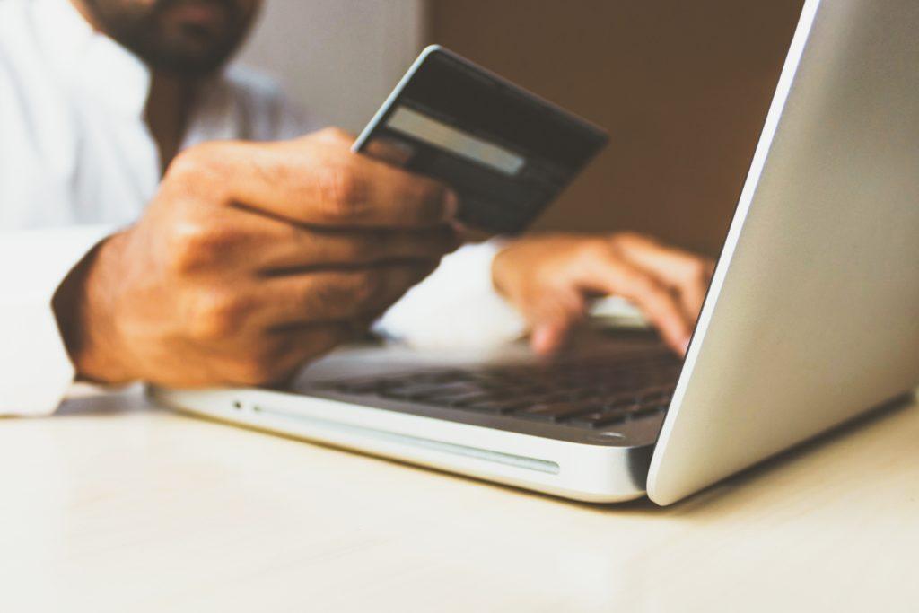 クレジットカードを見ながらPCで作業する男性