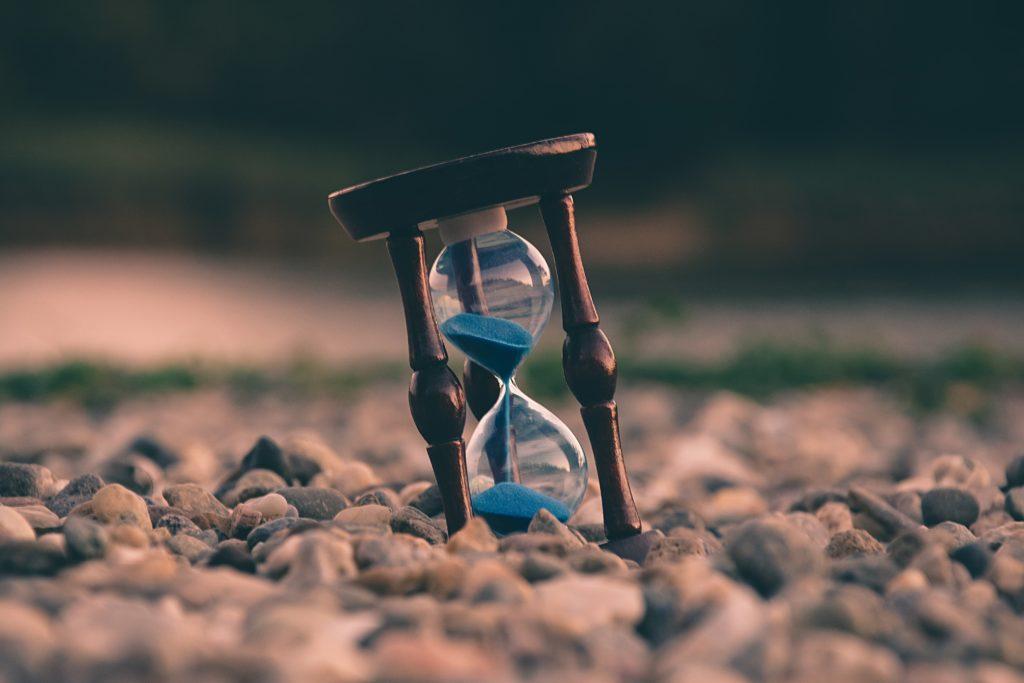 砂利の上の砂時計を見ながらアメリカ駐在を準備する