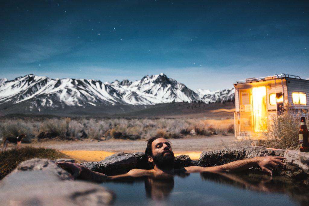 自然の中で温泉につかる男性