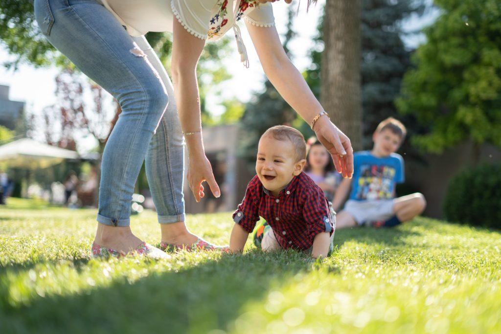 赤い服を着て芝生の上をハイハイをする赤ちゃん