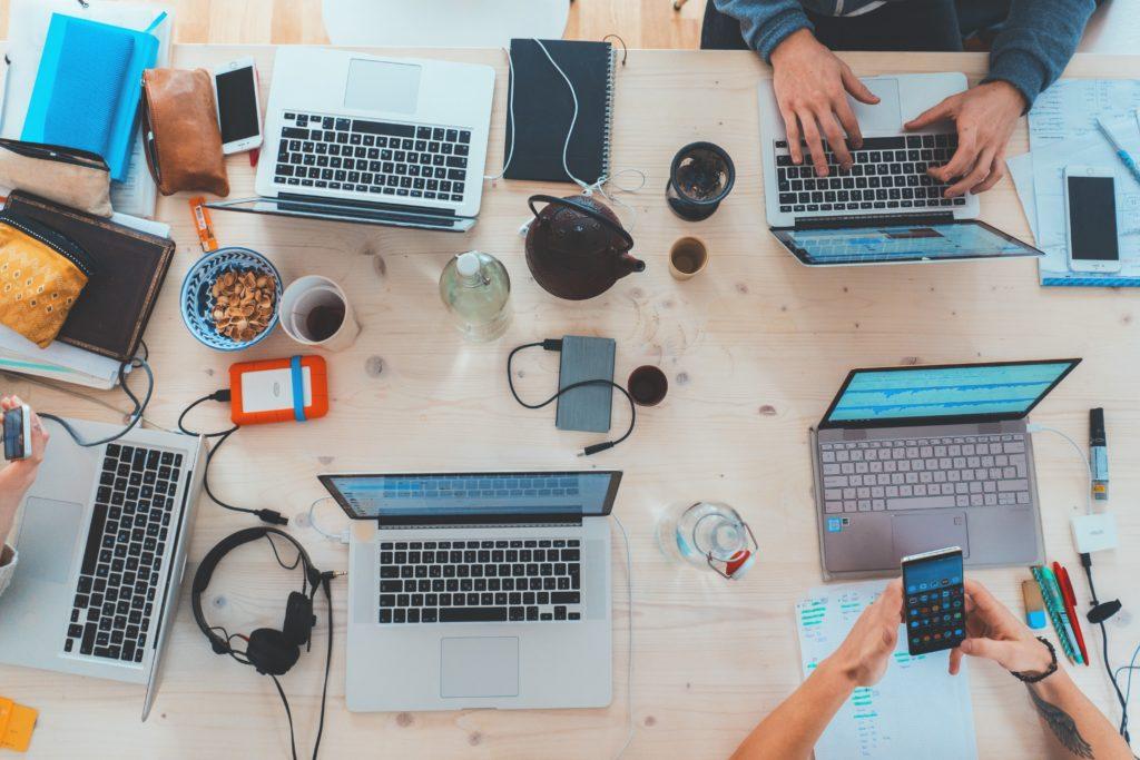デスクの上でPCで作業する人たち