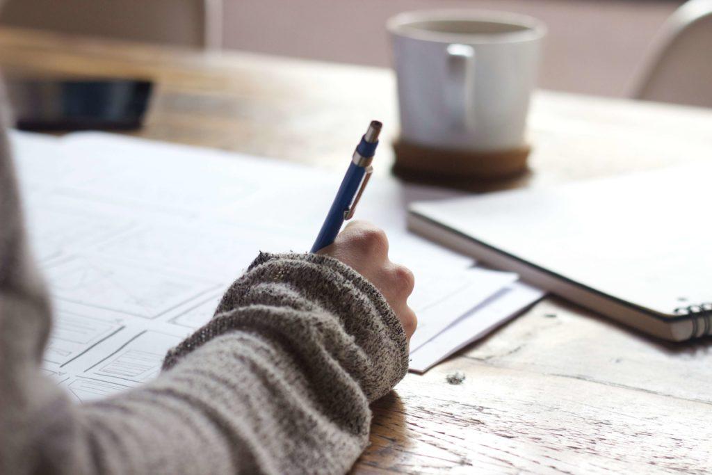 コーヒーを飲みながら英語を勉強する女性